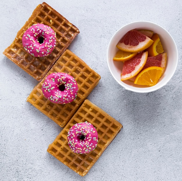 Draufsicht auf donuts auf waffeln mit zitrusfrüchten