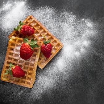 Draufsicht auf donuts mit erdbeeren und puderzucker