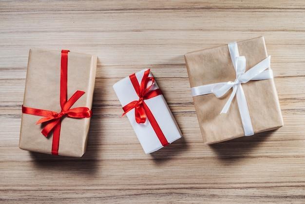 Draufsicht auf drei geschenkboxen, die in handwerk und weißes papier eingewickelt und mit satinbändern verziert werden