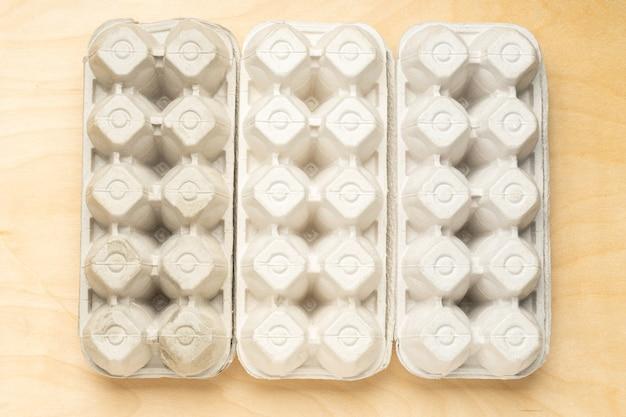 Draufsicht auf drei öko-ei-kartons auf holzhintergrund. null abfall. öko-ei-paket.