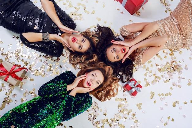 Draufsicht auf drei überraschte frau, die auf dem boden liegt und neujahr oder geburtstagsfeier feiert. tragen von luxus pailletten kleid und schmuck. golden glänzendes konfetti, rote geschenkboxen.