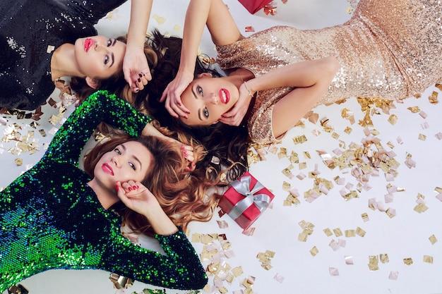 Draufsicht auf drei wunderschöne mädchen, die auf dem boden liegen und neujahr oder geburtstagsfeier feiern. tragen von luxus pailletten kleid und schmuck. golden glänzendes konfetti, rote geschenkboxen.