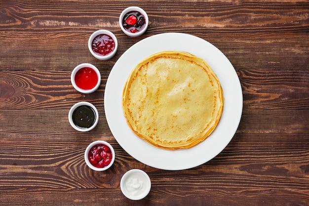 Draufsicht auf dünne pfannkuchen mit einer auswahl an marmelade und soße