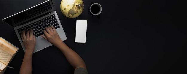 Draufsicht auf dunklem und schwarzem hintergrund mit hand, die an laptop und buch arbeitet und geographie und geschichte mit globalem erdkartenball, bildungs- und technologiekonzept lernt