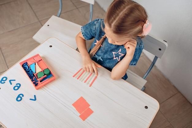 Draufsicht auf ein fokussiertes gelehrtes kind, das logisch komplexe kinderrätsel löst. entwicklung des kindes. gelehrsamkeitskonzept. foto mit lärm