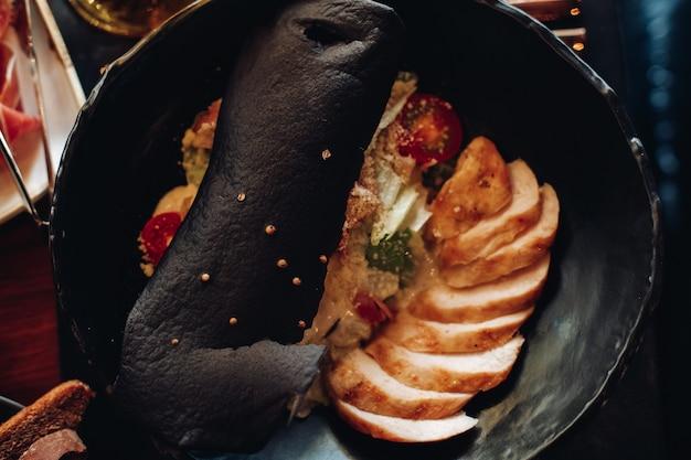 Draufsicht auf ein geschnittenes fleisch mit warmem gemüsesalat und einem großen stück brot oben. food-konzept