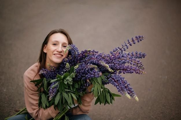 Draufsicht auf ein hübsches mädchen, das einen riesigen strauß wilder violetter lupinen hält, gekleidet in freizeitkleidung auf der straße