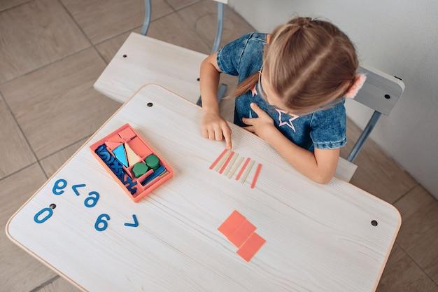 Draufsicht auf ein intelligentes konzentriertes kind, das logische komplexe kinderrätsel löst. entwicklung des kindes. wissenskonzept. foto mit lärm