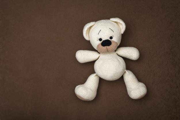 Draufsicht auf ein kleines weißes bärenjunges, das auf einem braunen hintergrund liegt. schönes strickspielzeug.