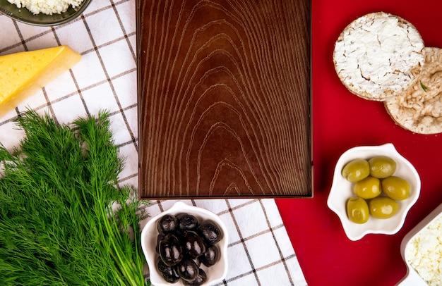 Draufsicht auf ein leeres holztablett und käse mit eingelegten oliven und reiskuchen auf kariertem stoff auf rot