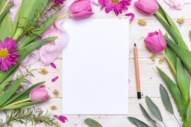 Draufsicht auf ein leeres papier und einen mit lila blumen verzierten bleistift