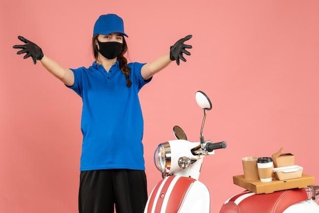 Draufsicht auf ein sich wunderndes kuriermädchen mit medizinischen maskenhandschuhen, das neben dem motorrad mit kaffeekuchen darauf auf pastellfarbener pfirsichfarbe steht