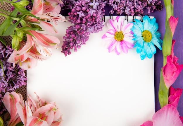 Draufsicht auf ein skizzenbuch und rosa und lila farbblumen gerbera-flieder-alstroemeria und gänseblümchenblumen auf sackleinen auf lila holzhintergrund