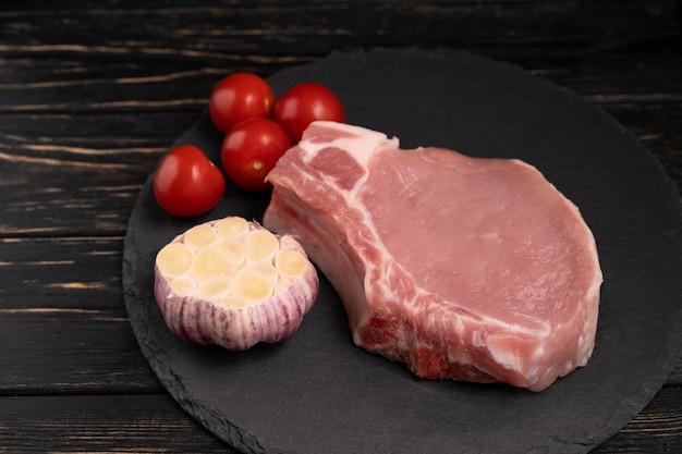 Draufsicht auf ein stück rohe schweinekotelettsteaks mit kirschtomaten und knoblauch auf einem schwarzen steinschneidebrett.