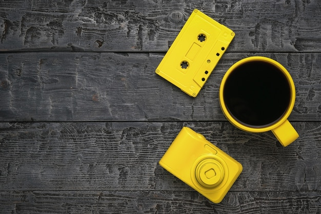 Draufsicht auf ein tonbandgerät, eine tasse kaffee und eine kamera auf einem holztisch. farben-trend.
