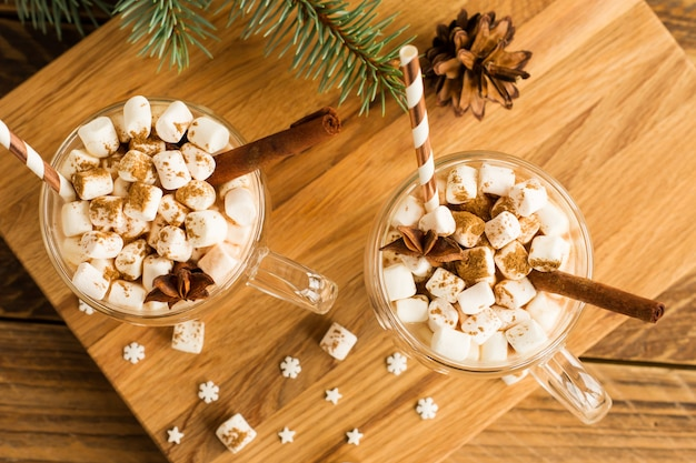 Draufsicht auf ein traditionelles schokoladen-weihnachtsgetränk mit marshmallows im glas auf einem hölzernen hintergrund abgeschnitten.