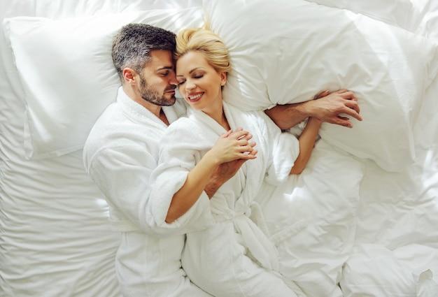 Draufsicht auf ein verliebtes paar mittleren alters in bademänteln auf flitterwochen, die in einem bett liegen und kuscheln.