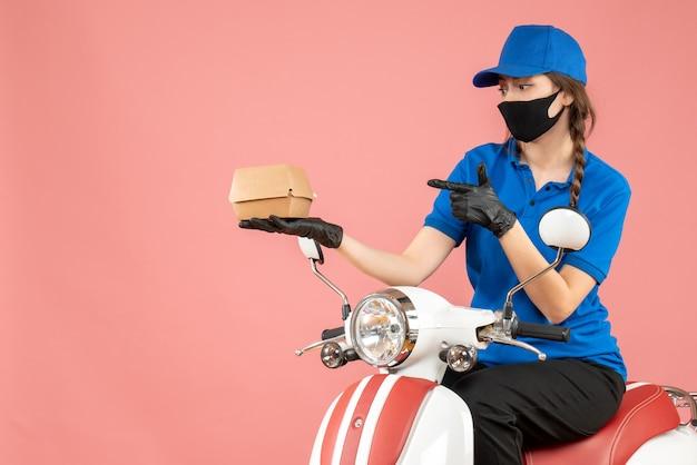 Draufsicht auf eine beschäftigte lieferperson mit medizinischer maske und handschuhen, die auf einem roller sitzt und bestellungen auf pastellfarbenem pfirsichhintergrund liefert