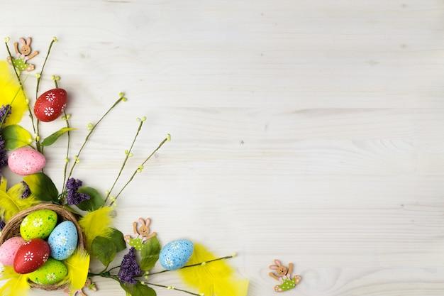 Draufsicht auf eine bunte ostereier und frühlingsblumen auf einem hellen holzhintergrund mit nachrichtenraum.