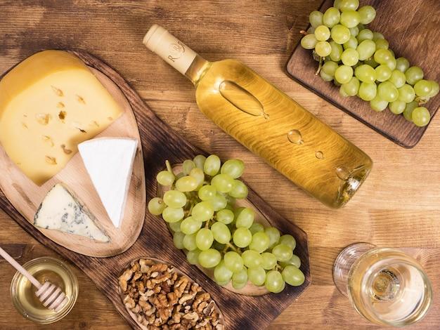 Draufsicht auf eine flasche weißwein neben frischen trauben auf holztisch. verschiedene käsesorten. französische küche.