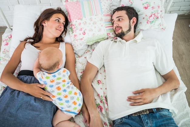 Draufsicht auf eine glückliche junge familie, vater und mutter liegen auf dem bett und plaudern mit ihrem kleinen charmanten halbjährigen baby.