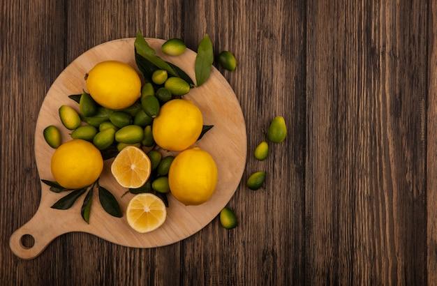 Draufsicht auf eine gute quelle von vitamin-c-zitronen, die auf einem hölzernen küchenbrett auf einer hölzernen oberfläche mit kopierraum isoliert werden