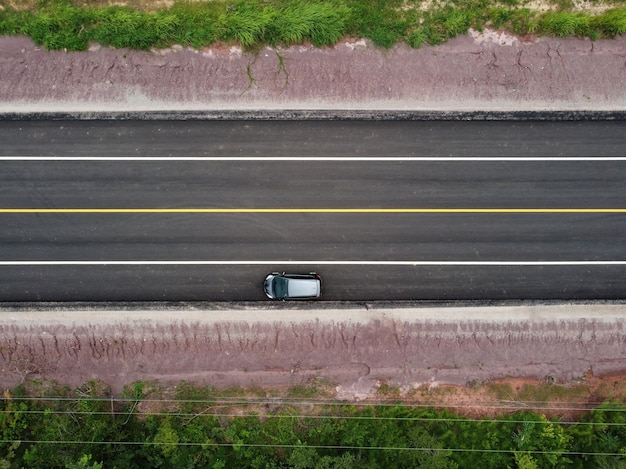 Draufsicht auf eine landstraße mit am straßenrand geparkten autos, drohnenluftaufnahme