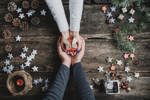 Draufsicht auf eine männliche hand, die weibliche hände hält, die kleine rote feiertagsgeschenkbox halten