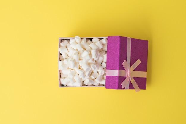Draufsicht auf eine offene geschenkbox mit marshmallows. ein süßer genuss. flach liegen.