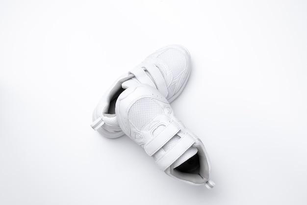 Draufsicht auf eine pyramide aus weißen kinderturnschuhen ein sneaker liegt auf einem anderen sneaker isoliert auf einem weißen...