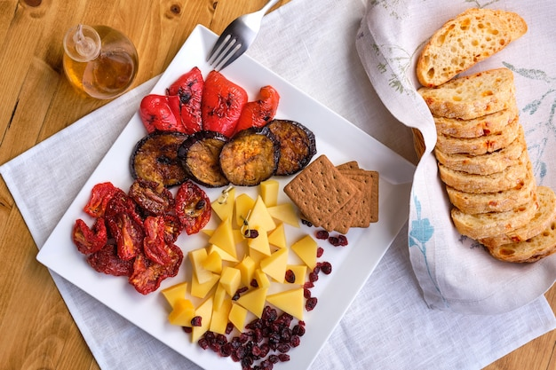 Draufsicht auf eine reihe verschiedener vorspeisen für wein - käse, sonnengetrocknete tomaten, geröstete auberginen, paprika, hardtack und getrocknete cranberry