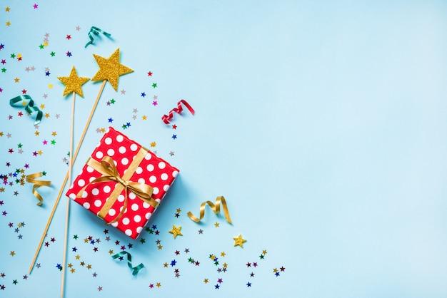 Draufsicht auf eine rot gepunktete geschenkbox, verstreute glitzernde sternförmige konfetti und bunte bänder auf blauem hintergrund. feierkonzept. speicherplatz kopieren.