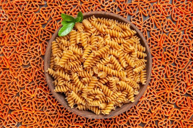 Draufsicht auf eine schüssel mit spirali-nudeln auf herzförmiger italienischer pasta auf dunklem tisch