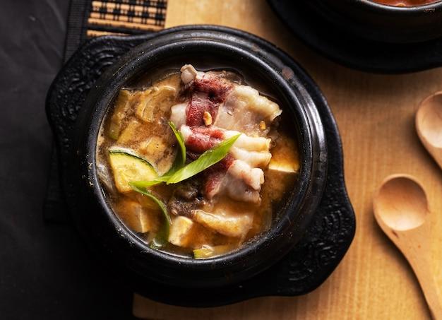 Draufsicht auf eine schüssel suppe mit schweinefleisch und zucchini auf dem tisch