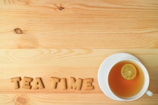 Draufsicht auf eine tasse heißen limetten-tee und kekse, die das wort teezeit auf holztisch buchstabieren