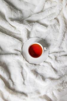 Draufsicht auf eine tasse heißen tee auf einem weißen bett in einem gemütlichen haus. vertikales foto. guten morgen.