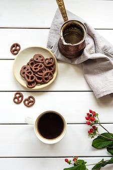 Draufsicht auf eine tasse kaffee, eine kaffeekanne und mit schokolade bedeckte brezeln auf einer weißen holzoberfläche. zusammensetzung des frühstücks oder der kaffeepause.