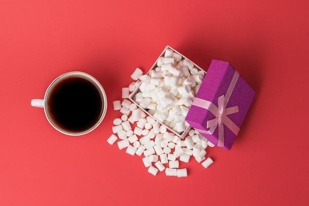 Draufsicht auf eine tasse kaffee und eine mit marshmallows gefüllte schachtel. ein süßer genuss. flach liegen.