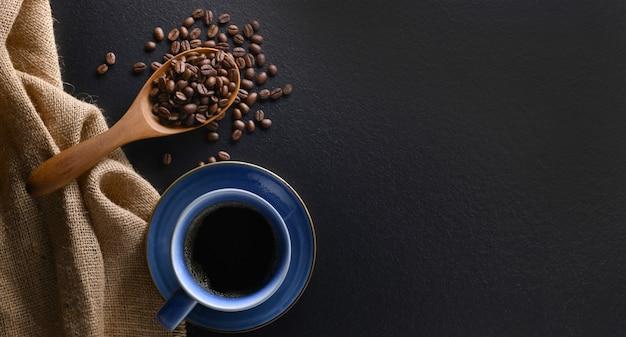 Draufsicht auf eine tasse kaffee und kaffeebohnen auf schwarzem hintergrund