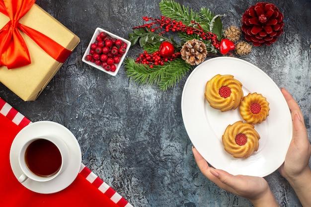 Draufsicht auf eine tasse schwarzen tee auf einem roten handtuch und hand, die kekse auf einem weißen teller hält neujahrsgeschenk mit rotem band auf dunkler oberfläche