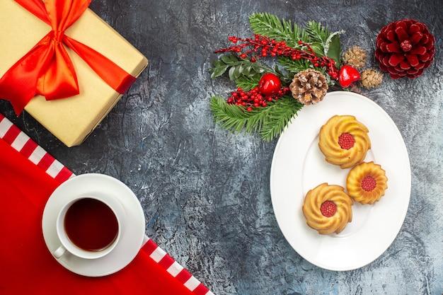 Draufsicht auf eine tasse schwarzen tee auf einem roten handtuch und kekse auf einem weißen teller neujahrsgeschenk mit rotem band auf dunkler oberfläche