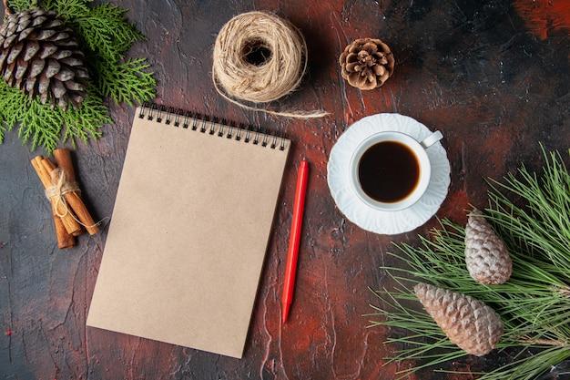 Draufsicht auf eine tasse schwarzen tee, geschlossenes notizbuch, zimtlimetten, eine kugel aus nadelbaumkegel auf dunklem hintergrund