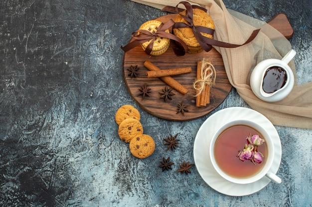 Draufsicht auf eine tasse schwarzen tee gestapelte kekse zimtlimetten auf eishintergrund