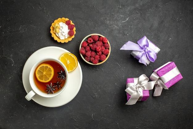 Draufsicht auf eine tasse schwarzen tee mit zitrone, serviert mit schokoladenhimbeere und geschenken auf dunklem hintergrund
