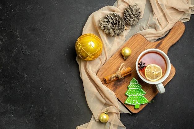 Draufsicht auf eine tasse schwarzen tee mit zitronen- und zimtlimetten dekorationszubehör für das neue jahr auf holzschneidebrett auf nacktem farbtuch