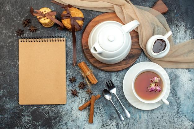 Draufsicht auf eine tasse schwarzen tee und wasserkocher auf holzbrett-notebook-keksen auf eishintergrund