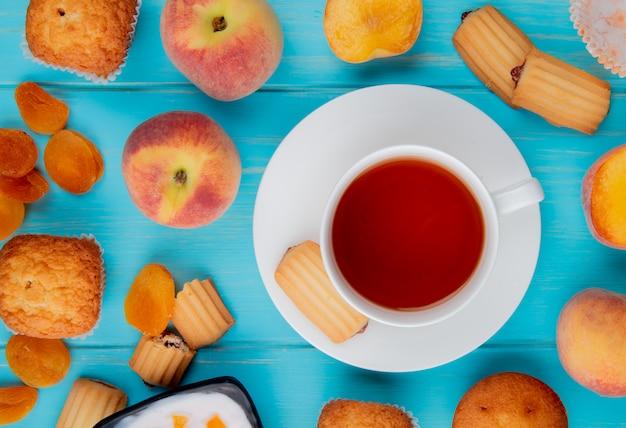 Draufsicht auf eine tasse tee mit keksen frische reife pfirsiche und getrocknete aprikosen auf blau