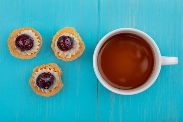 Draufsicht auf eine tasse tee mit mini-traubentörtchen lokalisiert auf einem blauen hölzernen hintergrund