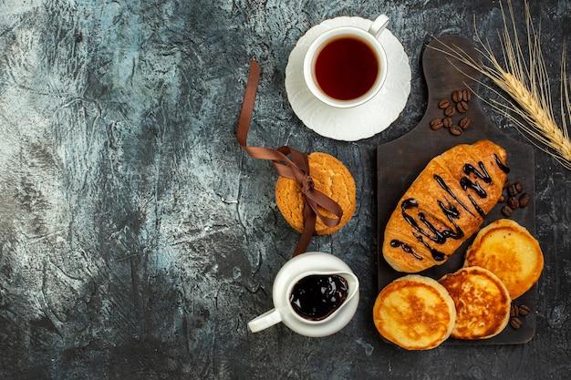 Draufsicht auf eine tasse tee und leckeres frühstück mit pfannkuchen-croisasant auf dunklem tisch