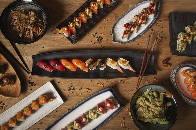Draufsicht auf eine vielzahl von sushi, nigiri, sashimi, yakisoba und edamame auf einem holztisch des restaurants